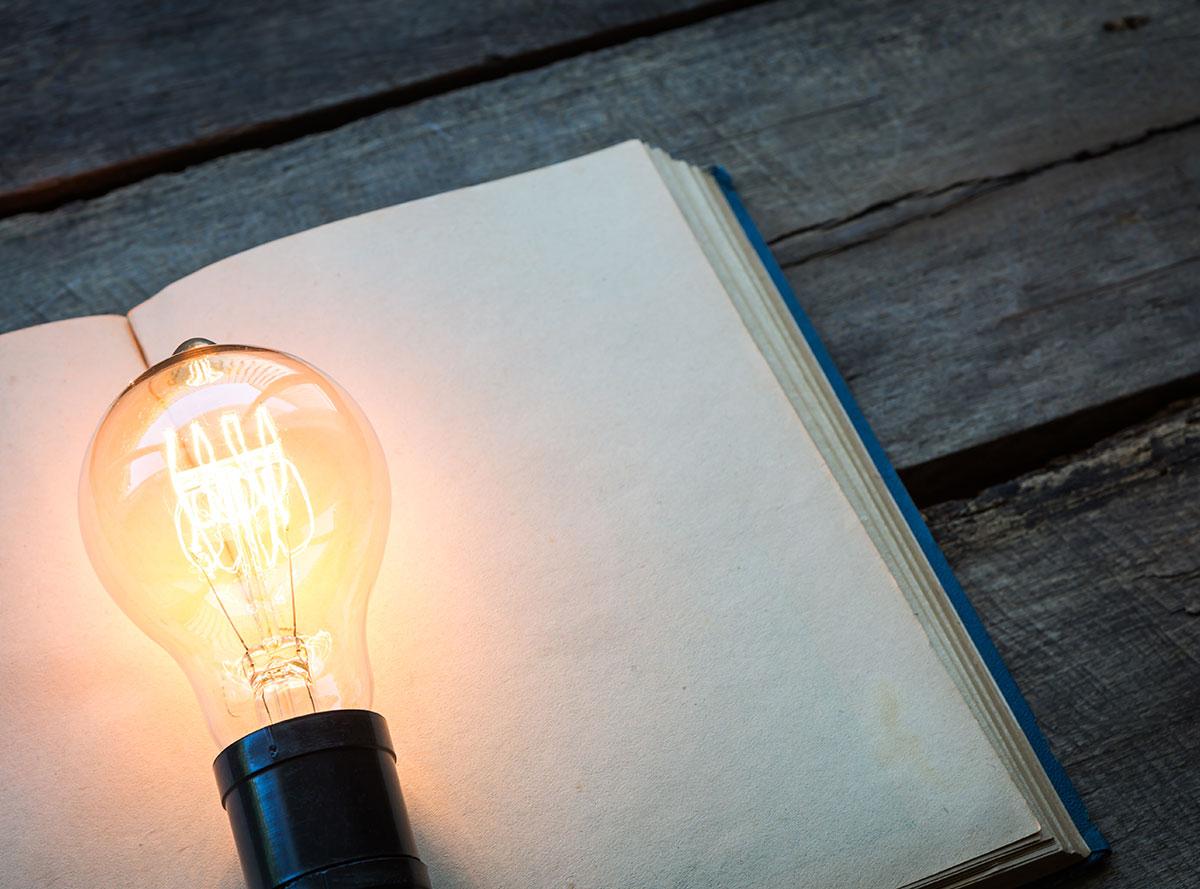 lit light bulb on top of book