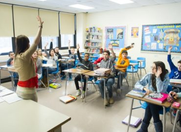 classroom of kids with hands raised