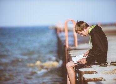 boy sitting on edge of dock reading