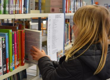 little girl pulling book from library shelf