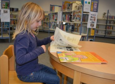 child sitting at table reading books