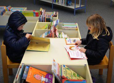 children sitting at book bin table
