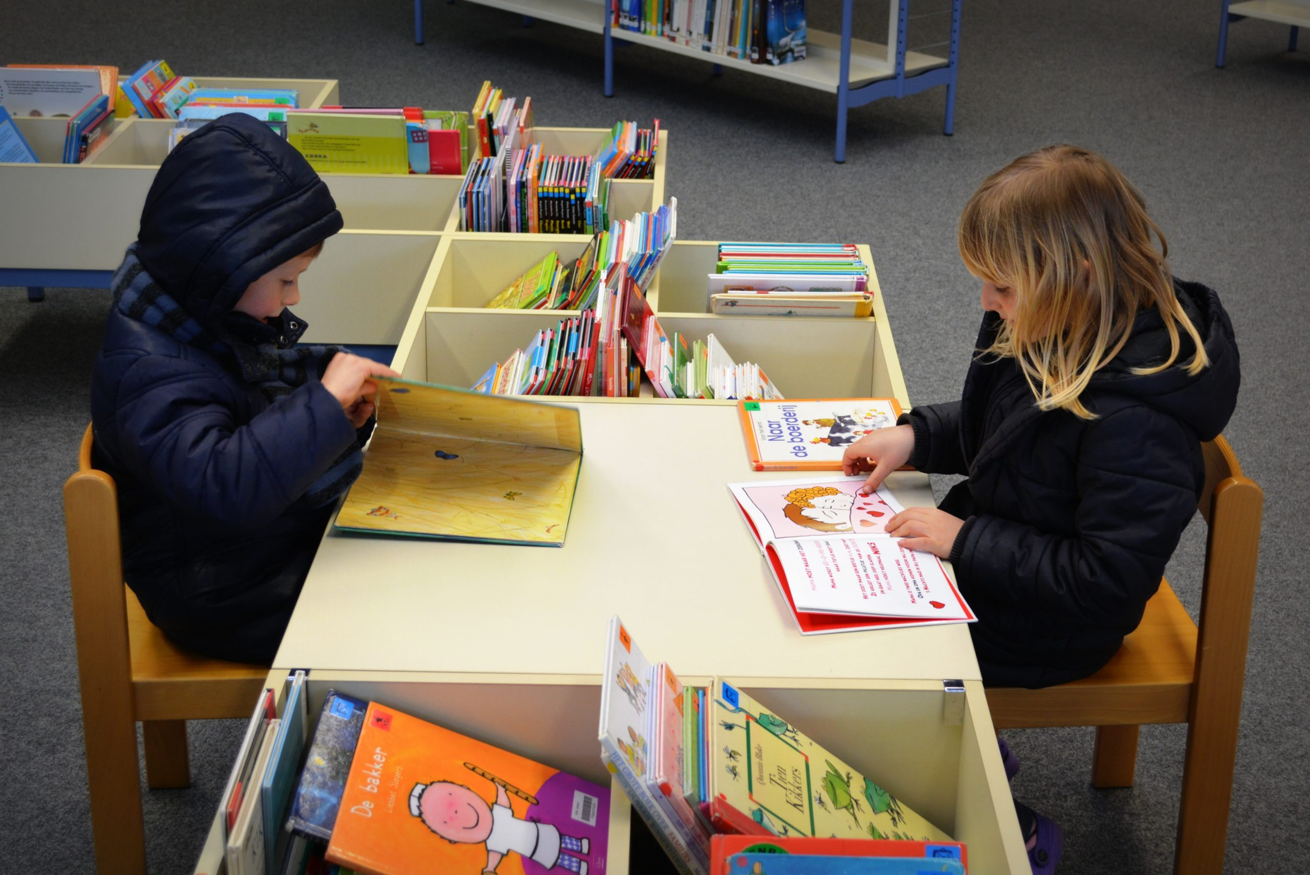 children sitting at book bin table