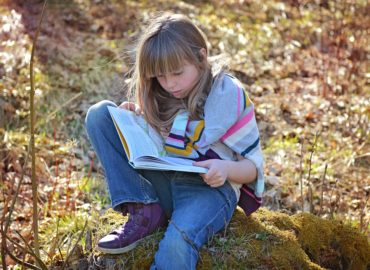 girl sitting on rock reading a book
