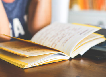 open book on table with person reading