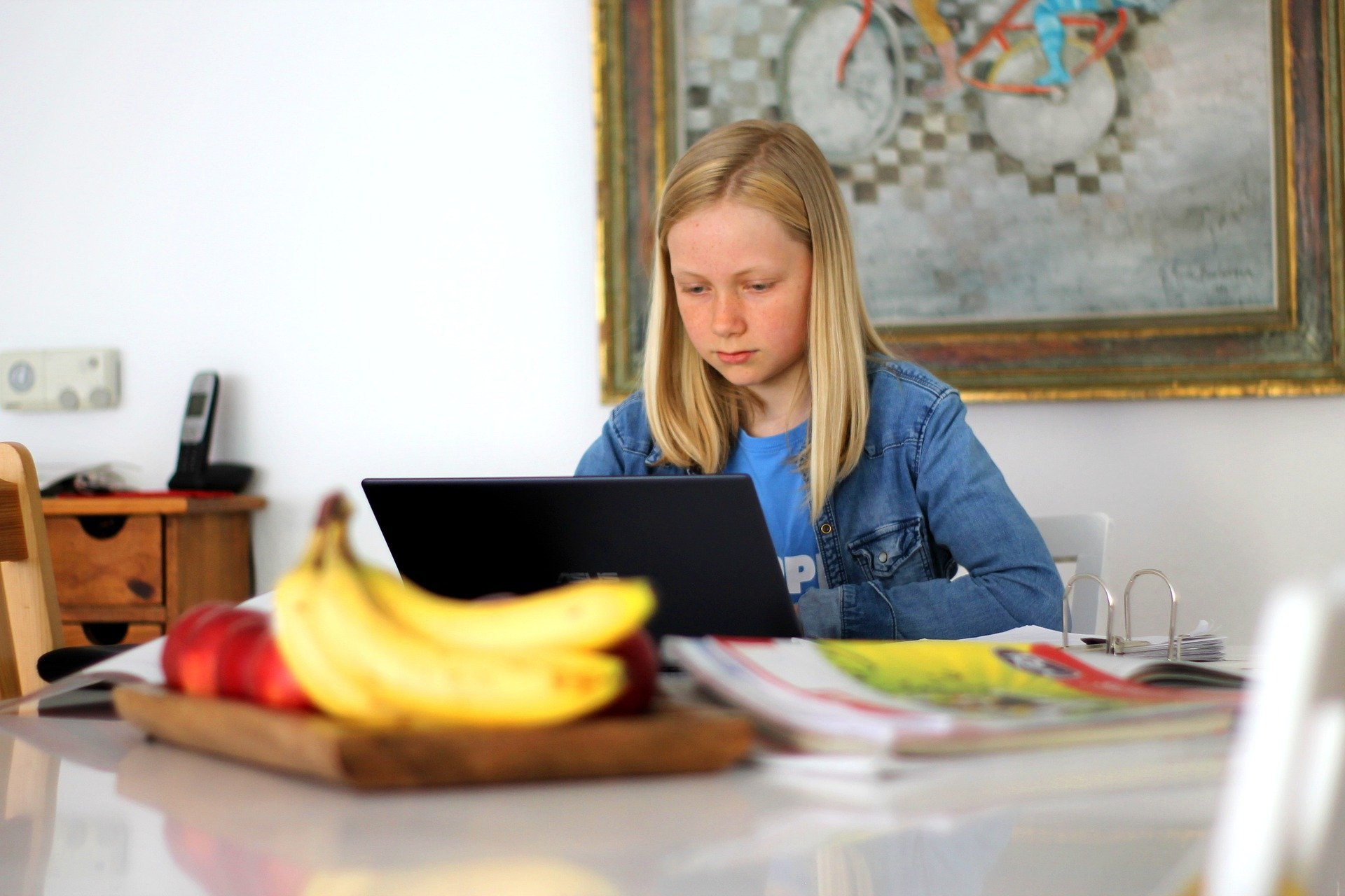 girl working on laptop in kitchen